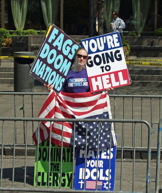 "Westboro church member holding offensive protest signs saying ""You're going to hell"" and ""Fags doom nations"""
